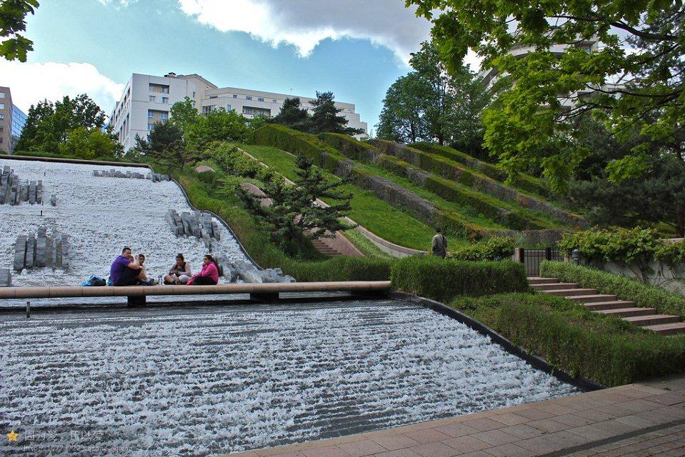 在充满了现代主义景观设计和雕塑作品的拉德芳斯区,狄德罗公园深陷在超现代的玻璃塔楼中犹如一颗翡翠明珠,它以汲取自古典园林的阿兰普罗沃斯风格结合水的美学,成为了拉德芳斯区独特的一景。 狄德罗公园是普罗沃斯中后期的作品,这一时期的普罗沃斯民经不再偏爱自然有机的形式,而是从几何形式中探求现代设计的语言。狄德罗公园的设计就表现出了爱到勒诺特尔式园林空间布局的影响。 从平面图上我们可以很容易地发现狄德罗公园的布局是一个传统的结构--中轴景观空间加两侧小花园空间。公园的平面是几何的,中轴线上是以水景为主题的序列景观,